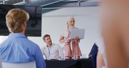 flanked : Front view of a young Asian businesswoman wearing a hijab holding a laptop and standing to address an audience, flanked by seated colleagues and delegates at a business conference. The back of the audience is visible in the foreground