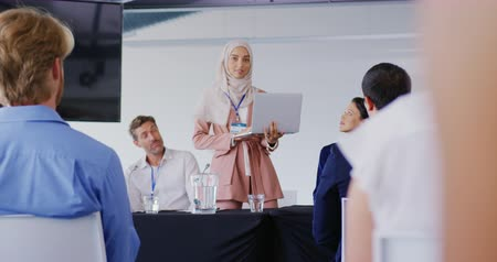 flanked : Front view of a young Asian businesswoman wearing a hijab holding a laptop, standing and gesturing as she addresses the audience at a business conference, flanked by seated colleagues and delegates, The back of the audience is visible in the foreground Stock Footage