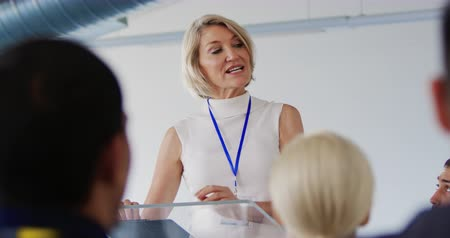 delegeren : Front view close up of a middle aged Caucasian businesswoman with blonde hair standing at a lectern gesturing while giving a presentation to the audience at a business conference Stockvideo