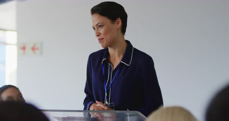 delegate : Front view close up of a young Caucasian businesswoman with short dark hair standing at a lectern addressing the audience at a business conference