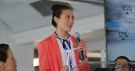 delegate : Side view close up of a young Asian businesswoman wearing a pink jacket standing at a lectern using a microphone to address the audience at a business conference. She is holding a model of a wind turbine. A young Caucasian man and woman sitting either sid