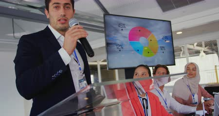 delegate : Front view close up of a young Caucasian businessman wearing a white shirt and black jacket standing at a lectern using a microphone to address the audience at a business conference. In the background is a screen with information on it and a diverse group