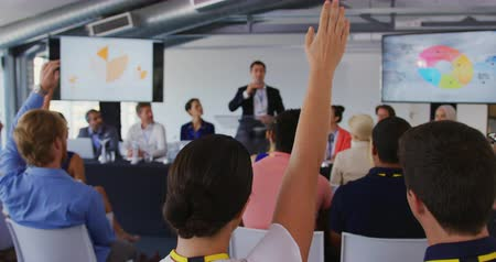 delegate : Back view close up of the seated audience at a business conference raising hands to ask questions, with a young Caucasian businessman standing on the stage with display screens showing information in the background