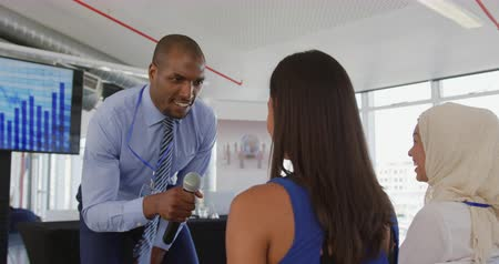 microphone : Side view close up of a young African American businessman standing and leaning to the front row of audience  at a business seminar, and using a microphone to interact with a young woman in the audience, seen from behind. The diverse front row of the audi