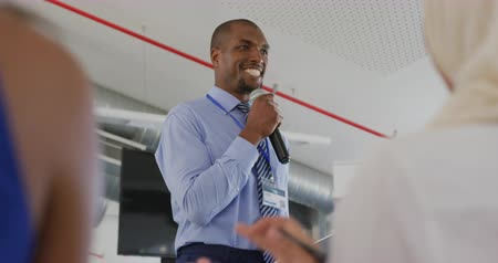delegate : Over the shoulder view of a young African American businessman standing in front row of the front row of an applauding audience, holding a tablet computer and addressing them with a microphone at a business seminar. Seen from audience perspective Stock Footage