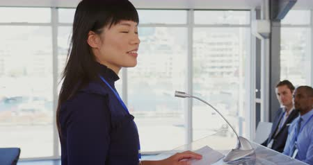 delegate : Side view close up of a young Asian businesswoman standing at a lectern addressing the audience at a business seminar and pointing. The diverse audience are visible sitting and listening in the background