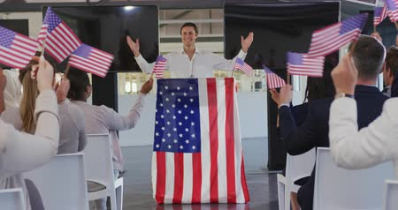 electioneering : Front view of a smiling young Caucasian man standing on a podium decorated with a US flag at a political rally, with the audience seen from the back waving flags in support in the foreground Stock Footage
