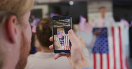 election campaign : Over the shoulder view of a Caucasian man holding a smartphone and filming a speaker standing on a podium decorated with a US flag at a political rally, and the audience waving flags Stock Footage