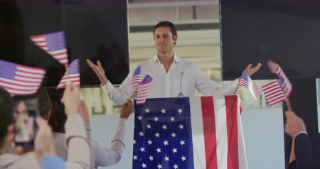 candidato : Front view close up of a smiling young Caucasian man standing on a podium decorated with a US flag at a political rally, with the audience seen from the back waving flags in support in the foreground