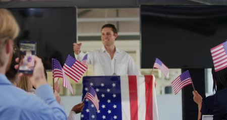 electioneering : Front view of a smiling young Caucasian man standing on a podium decorated with a US flag at a political rally, with the audience seen from the back holding flags in support in the foreground. A member of the audience is filming the event on his smartphon