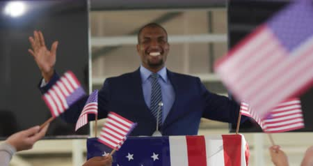 electioneering : Front view of a smiling young African American man standing on a podium decorated with a US flag smiling and raising his arms in triumph at a political rally, with the arms of the audience seen from the back waving flags in the foreground