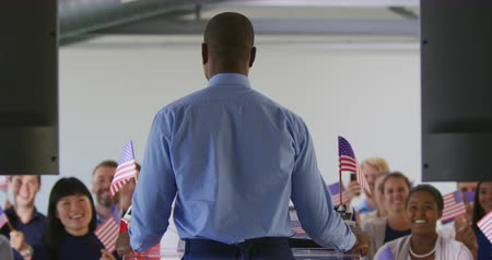 election campaign : Back view close up of a young African American man standing on a podium and raising his arms as he addresses the audience at a political rally, with the audience visible smiling and waving flags in support in the background Stock Footage