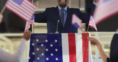候補者 : Front view of a young African American man standing on a podium decorated with a US flag smiling and shaking his fists in triumph at a political rally, with the arms of the audience seen from the back
