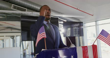 election campaign : Side view close up of a smiling young African American man standing on a podium decorated with a US flag shouting and pumping his fist in triumph at a political rally