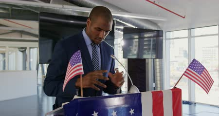 electioneering : Side view close up of a serious young African American man standing at a lectern decorated with a US flags addressing the audience at a political rally