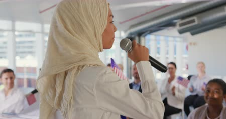 képviselő : Side view close up of a young Asian woman wearing a hijab standing with a microphone pointing and addressing the audience at a political convention, with the audience visible in the background listening and holding US flags Stock mozgókép