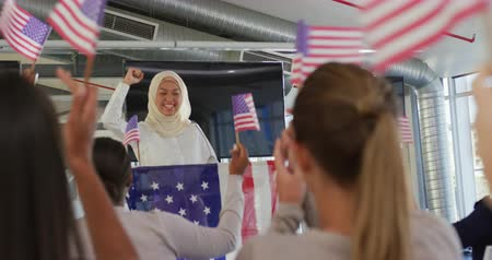 négy : Front view of a smiling young Asian woman wearing a hijab standing at a lectern decorated with a US flag and raising her fist in triumph at a political rally, with the audience seen from the back waving flags in support in the foreground Stock mozgókép