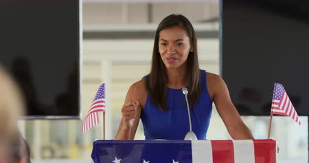 electioneering : Front view of a smiling young mixed race woman standing at a lectern decorated with US flags raising her fist and addressing the audience at a political rally