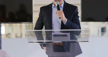 yoğunlaşarak : Front view close up of a middle aged Caucasian businessman standing at a lectern using a microphone to address the audience at a business convention