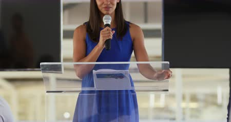 delegate : Front view close up of a young mixed race businesswoman standing at a lectern using a microphone to address the audience at a business convention