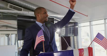 electioneering : Side view close up of a smiling young African American man standing on a podium decorated with a US flag shouting and raising his fist in triumph at a political rally
