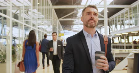 delegate : Front view close up of a middle aged Caucasian businessman holding a coffee and walking through a modern foyer to a business conference. Other business delegates can be seen walking in the background