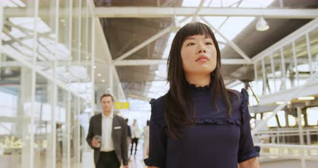 delegate : Front view close up of a young Asian businesswoman holding a smartphone walking through a modern foyer to a business conference. Other business delegates can be seen walking in the background