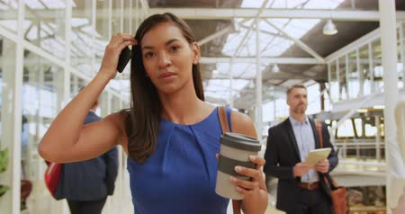 arriving : Front view close up of a young mixed race businesswoman holding a smartphone and a coffee walking through a modern foyer to a business conference. Other business delegates can be seen walking in the background