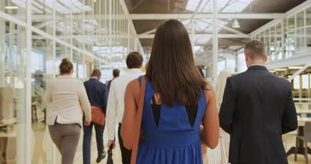 delegate : Rear view of a diverse group of business delegates walking through a modern foyer to a business conference