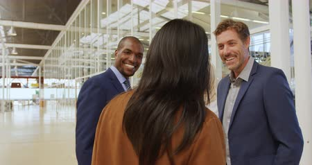 colegas de trabalho : Rear view close up of a businesswoman walking and greeting a young African American and a young Caucasian businessman talking with a young Asian businesswoman wearing a hijab in a modern foyer outside a business conference