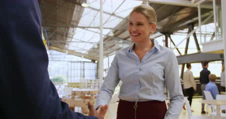 socialising : Front view close up of a young Caucasian businesswoman walking up to and shaking the hand of a businessman in a modern foyer outside a business conference Stock Footage