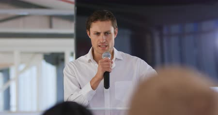 delegeren : Front view close up of a young Caucasian businessman standing at a lectern gesturing and using a microphone to address the audience at a business convention Stockvideo
