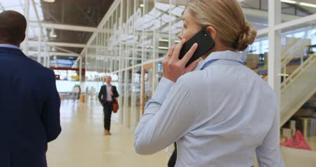 delegate : Back view close up of a young Caucasian businesswoman making a call on a smartphone as she walks in the foyer at a business conference. Other business delegates can be seen walking in the background Stock Footage