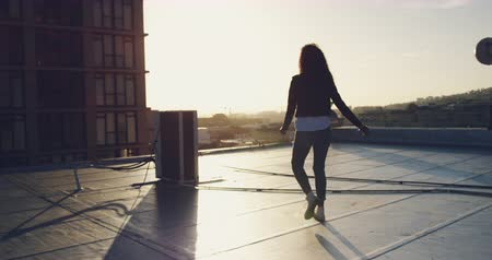 estilo livre : Back view of a hip young mixed race woman running on an urban rooftop with buildings in the background, arms outstretched, backlit by sunlight