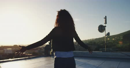 długi : Back view of a hip young mixed race woman standing on an urban rooftop with buildings in the background, arms outstretched, backlit by sunlight