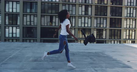 estilo livre : Side view of a hip young mixed race woman running on an urban rooftop with a building in the background, throwing her jacket