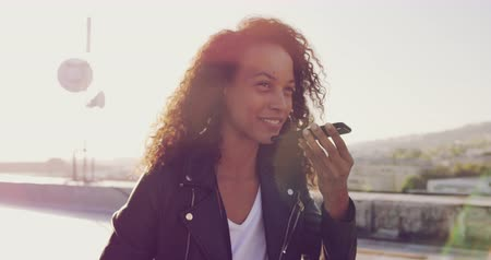 boky : Front view close up of a hip young mixed race woman sitting and talking on her smartphone on an urban rooftop with buildings in the background, backlit by sunlight