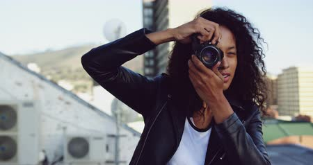 on camera : Front view close up of a hip young mixed race woman taking photos with a camera on an urban rooftop with buildings in the background Stock Footage