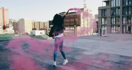 grenade : SIde view of a hip young mixed race woman walking and using smoke grenade on an urban rooftop with buildings in the background
