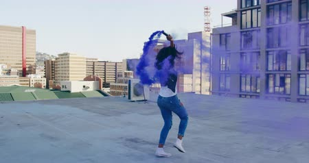 grenade : Side view of a hip young mixed race woman running and using smoke grenade on an urban rooftop with buildings in the background