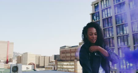 grenade : Front view of a hip young mixed race woman smiling and using smoke grenade on an urban rooftop with buildings in the background Stock Footage