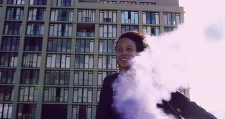 grenade : Front view of a hip young mixed race woman smiling and using smoke grenade on an urban rooftop with a building in the background, backlit by the sunlight Stock Footage