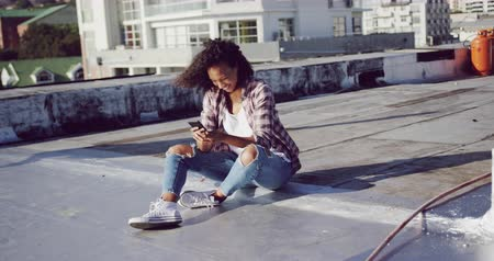 estilo livre : Front view of a hip young mixed race woman sitting and using her smartphone on an urban rooftop with buildings in the background