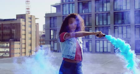 granada : Front view close up of a hip young mixed race woman standing and using smoke grenade on an urban rooftop with buildings in the background