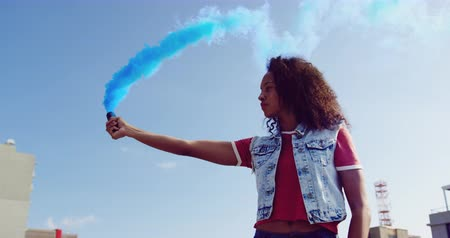 denim : Side view close up of a hip young mixed race woman standing and using smoke grenade on an urban rooftop with buildings in the background