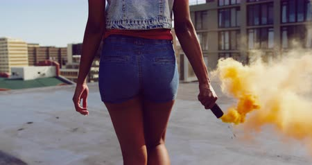 grenade : Back view close up of a hip young mixed race woman walking and using smoke grenade on an urban rooftop with buildings in the background