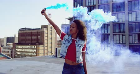 grenade : Front view close up of a hip young mixed race woman standing and using smoke grenade on an urban rooftop with buildings in the background