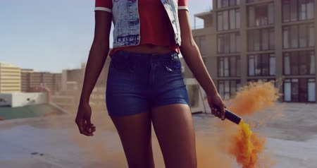 grenade : Front view close up of a hip young mixed race woman walking and using smoke grenade on an urban rooftop with buildings in the background Stock Footage