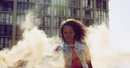 grenade : Front view close up of a hip young mixed race woman standing and using smoke grenade on an urban rooftop with a building in the background