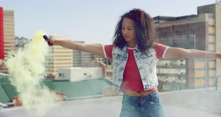 granada : Front view close up of a hip young mixed race woman standing and using smoke grenade on an urban rooftop, looking to camera, with buildings in the background